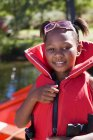 Girl wearing red life jacket and smiling with defocussed background — Stock Photo