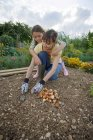 Mother and daughter planting bulbs with trowel in garden — Stock Photo