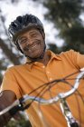 Active senior man wearing orange polo shirt and cycling helmet, sitting on bicycle in park — Stock Photo