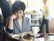 Vue de face de livre de lecture de femme à table de café, mettant l'accent sur le premier plan — Photo de stock