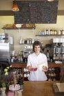 Официантка, выступающей за счетчик в кафе, держа большая кружка, ложка и салфеток — стоковое фото