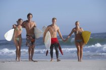 Two young couples holding hands during walking at beach with surfboards — Stock Photo