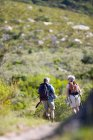 Rear view of senior couple with rucksacks hiking on mountain trail — Stock Photo