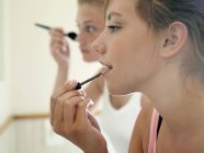 Girls applying make-up and looking at reflection in mirror — Stock Photo