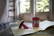 Small tin of pink paint and paintbrush — Stock Photo