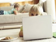 Girl lying on sofa at home, focus on boy lying on floor and using laptop — Stock Photo