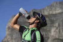 Closeup of male mountain biker drinking from water bottle — Stock Photo