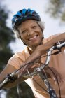 Active senior woman wearing polo shirt and cycling helmet, sitting on bicycle in park — Stock Photo