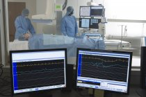 Doctors scanning patient in hospital, visual monitors in foreground — Stock Photo
