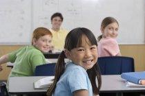 Lehrer Whiteboard im Klassenzimmer, Schwerpunkt Kinder am Schreibtisch saß — Stockfoto