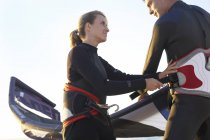 Low angle view of young smiling couple in wetsuits standing on beach with kiteboard at sunset — Stock Photo