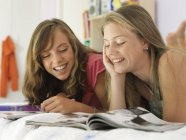 Two teenage girls lying on bed and reading magazines — Stock Photo