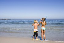 Boy and girl standing side by side on sandy beach at waters edge — Stock Photo