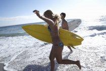 Вид збоку друзів працює в серфінгу на пляжі і проведення дошки для серфінгу — стокове фото