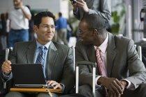 Due uomini d'affari che si siede nel terminal dell'aeroporto, che utilizza computer portatile — Foto stock