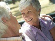 Smiling senior couple sitting in convertible car — Stock Photo
