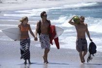 Трое друзей, ходить на пляж, пара с доски для серфинга, взявшись за руки, человек нося арбуз — стоковое фото