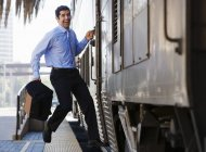Businessman hurrying to catch passenger train, leaping with briefcase — Stock Photo