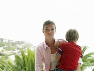 Portrait of young woman standing on balcony and holding son at daytime — Stock Photo
