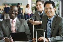 Tre genti di affari seduti in aeroporto terminal con computer portatile e bagagli — Foto stock