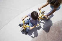 Overhead view of boy and girl riding toy tricycle and pushing scooter in playground — Stock Photo