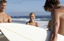 Four young friends standing on beach near water's edge, carrying surfboards, smiling — Stock Photo