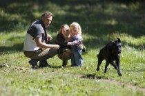 Geração de duas família vendo cachorro correndo no campo, mãe filha abraça — Fotografia de Stock