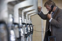 Side view of businessman using public payphone, focus on background — Stock Photo