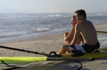 Side view of young couple sitting beside windsurfers on sandy beach, looking at horizon over sea — Stock Photo