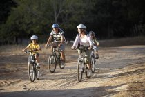 Two generation family cycling on dirt track in countryside — Stock Photo