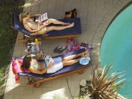 Two teenage girls relaxing on sunloungers beside pool, reading magazines — Stock Photo