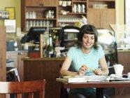Frau, Studium an der Café-Tisch und anhören von MP3-player — Stockfoto