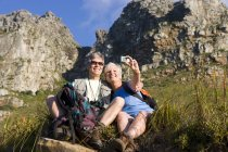 Mature couple sitting on mountain slope, woman taking self-portrait with digital camera — Stock Photo