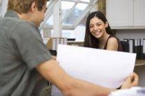 Молодий підприємець працює на столі в офісі, зосередитися на бізнес-леді у фоновому режимі, посміхаючись, портрет — стокове фото