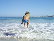 Rear view of boy jumping into surf at beach — Stock Photo