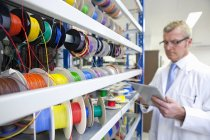 Engineer taking inventory of vibrant wire spools on digital tablet in laboratory — Stock Photo