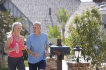 Active senior couple in sportswear jogging along suburban street, woman holding plastic water bottle — Stock Photo