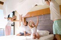 Eltern, die Erziehung Bettlaken in Luft über Sohn und Tochter im Schlafzimmer — Stockfoto