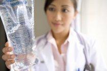 Vista frontale del medico femminile che tiene la borsa Iv — Foto stock