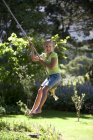 Side view of girl swinging on garden rope swing and smiling — Stock Photo