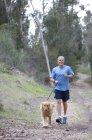 Homme senior actif en bleu t-shirt et Short marchant golden retriever le long du sentier forestier — Photo de stock
