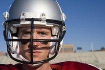 Giocatore di football americano indossando striscia di calcio e casco protettivo in piedi sul campo — Foto stock
