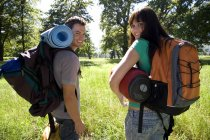 Couple carrying rucksacks and sleeping bags and standing in woodland — Stock Photo