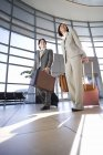 Businessman and businesswoman walking with luggage in tow in airport, building entrance in background — Stock Photo