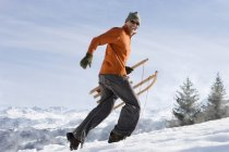 Side view of man carrying sled in snow, mountain range in background — Stock Photo