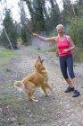 Femme senior active en rose sport veste et des jambières en cours d'exécution avec golden retriever le long du sentier forestier — Photo de stock