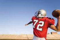 Zagueiro de futebol americano na faixa vermelha prestes a jogar a bola durante o jogo do competidor — Fotografia de Stock