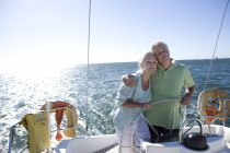 Mature couple standing at helm of yacht — Stock Photo