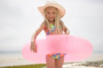Portrait of young girl smiling with pink inflatable on beach — Stock Photo