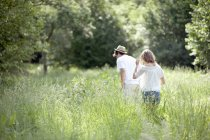Young couple walking through meadow in countryside — Stock Photo